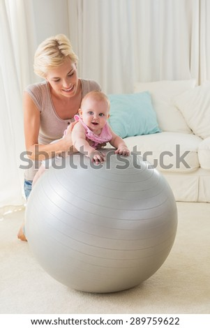 Happy mother with her baby girl in the exercice ball at home in the living room - stock photo