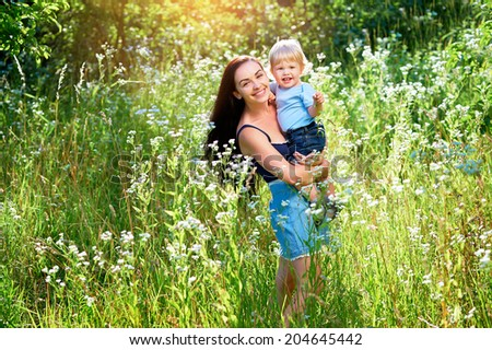 Happy mother with her child playing in white flowers. - stock photo