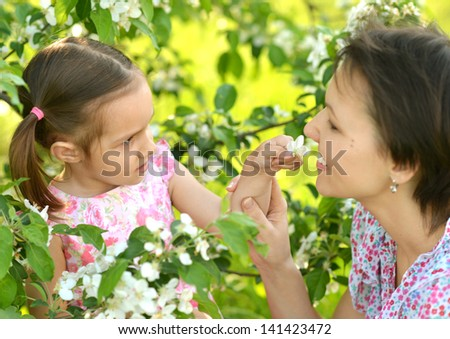 happy mother with her daughter walk in the park in summer