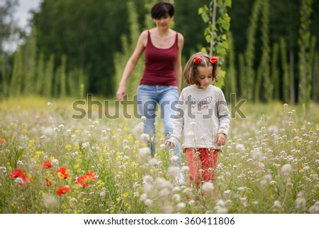 Happy mother with her little daughter in poppy field