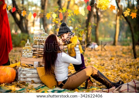Happy mother with her little son playing in the park - stock photo