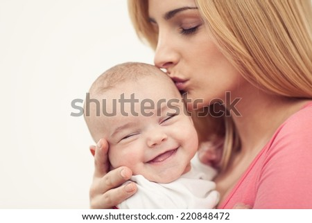 Happy mother with her 3 months old daughter. - stock photo