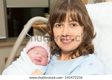 Happy Mother with Her Newborn Baby Girl on Hospital Bed - stock photo