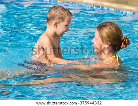 happy mother with her son in swimming pool