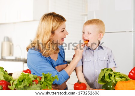 Happy mother with her son in the kitchen - stock photo