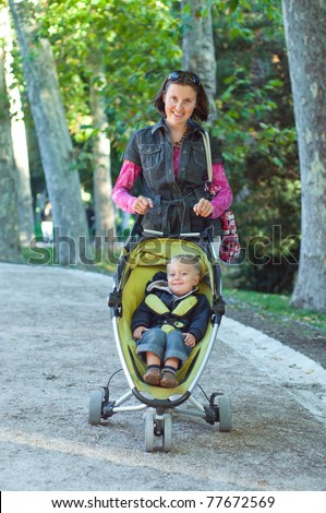 Happy mother with her son walking in the park in the summer day. Vertical view