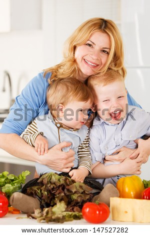 Happy mother with her sons having fun in the kitchen