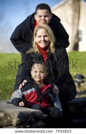 Happy mother with her two sons outdoor portrait - stock photo