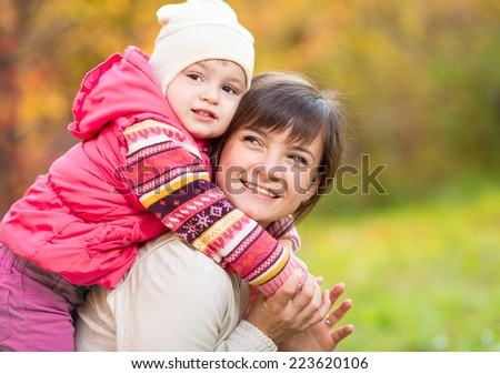 happy mother with kid girl outdoor in autumn park - stock photo