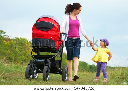 happy mother with little daughter and pram are walking in park - stock photo