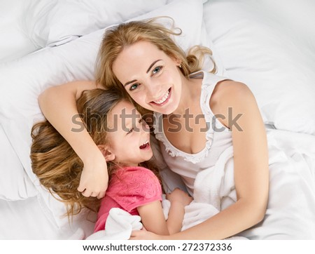 happy mother with little daughter on white bed, shot from above - stock photo
