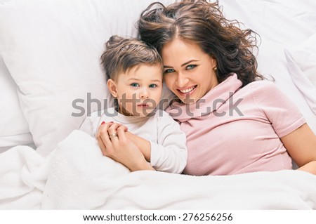 happy mother with little son on white bed, shot from above - stock photo