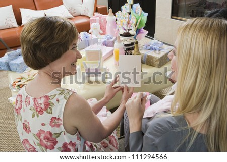 Happy mother with pregnant daughter reading greeting card at a baby shower