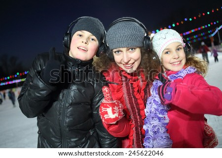 Happy mother with son and daughter make excellent gesture on the silent disco skating  - stock photo