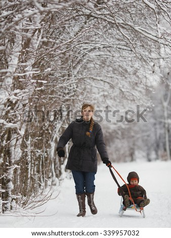 happy mother with son in winter park with sled - stock photo