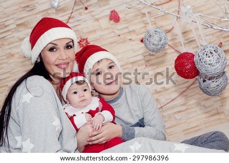 Happy mother with sons in Santa hats - stock photo
