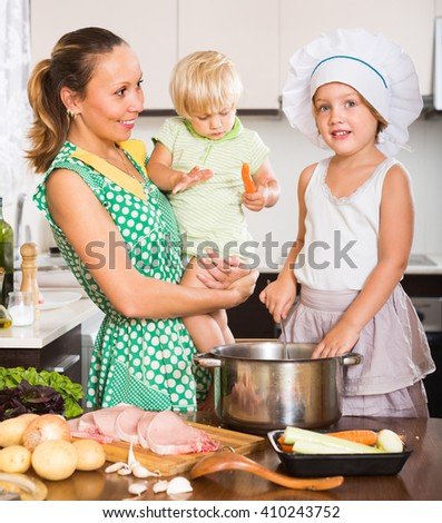 Happy mother with two daughters cooking at home kitchen. Focus on girl - stock photo