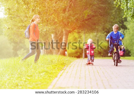 happy mother with two kids on scooter and bike in the park, family sport - stock photo