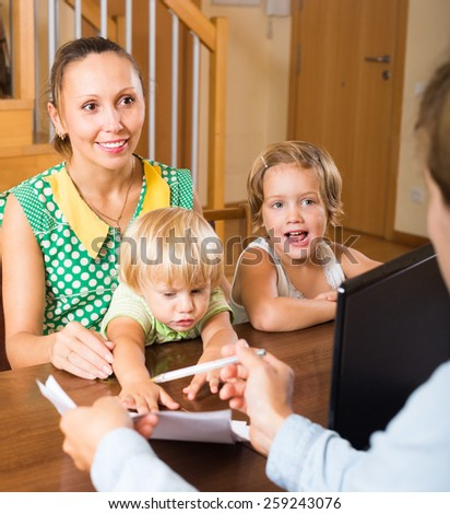 Happy mother with two playful children glad hearing words of social worker at home - stock photo