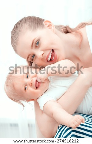 Happy motherhood! Young smiling mother holding her baby watching at you while the child laughing  - stock photo