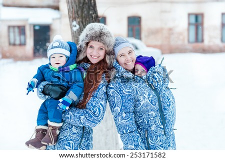 Happy mothers and babys playing on snow in winter park - stock photo