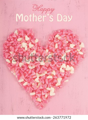 Happy Mothers Day gift of pink jelly candy in heart shape with sample text, and applied retro vintage style filters. - stock photo
