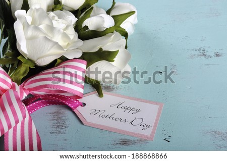 Happy Mothers Day gift of white roses bouquet with pink stripe ribbon and gift tag with greeting on aqua blue vintage shabby chic table. - stock photo