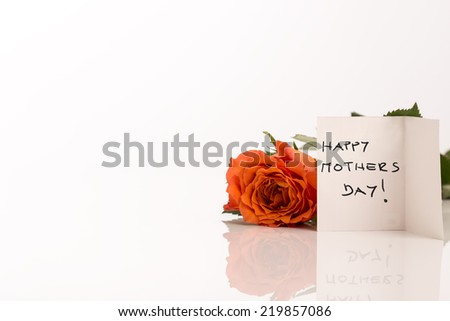Happy Mothers Day greeting card background with a single symbolic fresh  rose and a handwritten note on a white reflective surface with copyspace for your greeting or wishes. - stock photo