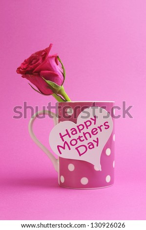 Happy Mothers Day heart gift tag on pink polka dot coffee mug with pink rose bud. - stock photo