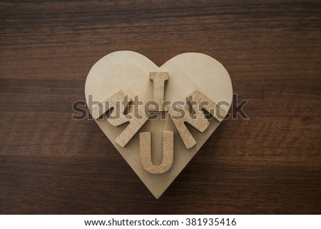 Happy Mothers day. I Love my mum Concept. Wood heart and Wooden letters spelling. Image with shadows on table. - stock photo