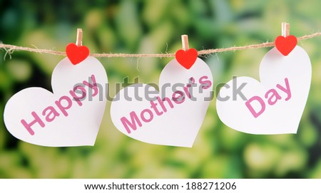 Happy Mothers Day message written on paper hearts with flowers on bright background - stock photo