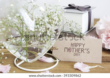Happy mothers day on paper tag with gypsophila flowers in heart bottle on wooden table