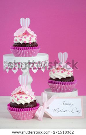 Happy Mothers Day pink and white cupcakes on retro style cake stands on vintage white wood table. - stock photo