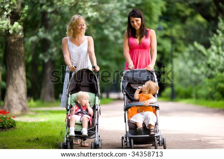 Happy mothers walking together with kids in prams - stock photo