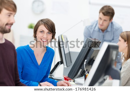 Happy motivated attractive young businesswoman sitting at her desk in a busy office giving the camera a bright friendly smile - stock photo