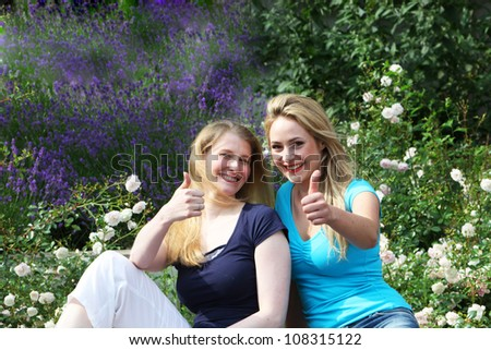 Happy motivated friends giving thumbs up Happy motivated friends sitting close together amongst garden flowers giving thumbs up of approval and hope - stock photo