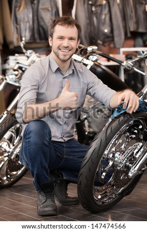 Happy motorcycle owner. Cheerful young men crouching near his new motorcycle - stock photo