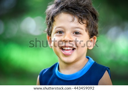 Happy mulatto boy child is smiling enjoying adopted life. Portrait of young boy in nature, park or outdoors. Concept of happy family or successful adoption or parenting. - stock photo