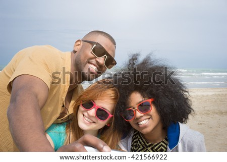 Happy multi-ethnic best friends posing for selfie photo with toothy smiles and having fun on the beach - stock photo
