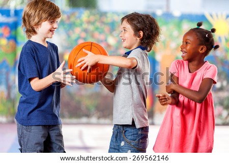 Happy multi ethnic children playing basketball at school. - stock photo