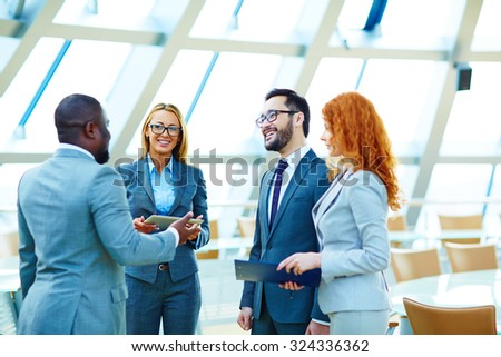 Happy multi-ethnic colleagues talking in office - stock photo