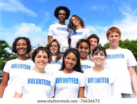 happy multi-ethnic volunteer group outdoors - stock photo