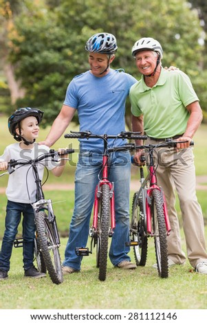 Happy multi generation family on their bike at the park on a sunny day - stock photo