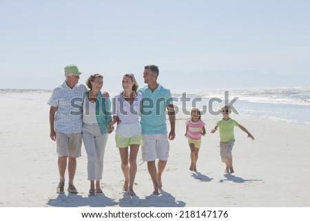 Happy multi-generation family walking on sunny beach - stock photo