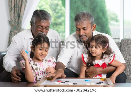 Happy multi generations Asian Indian family playing carrom game at home. Grandparent, parent and children indoor lifestyle. - stock photo
