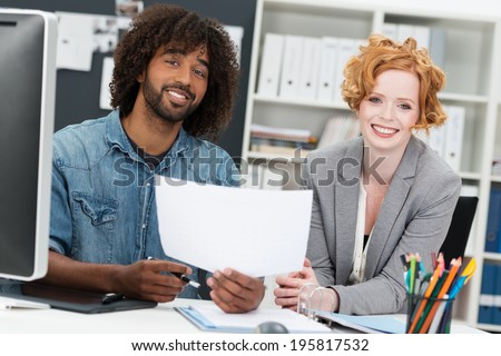 Happy multiethnic business partners sitting together in the office with a casual young African American man and beautiful redhead woman discussing a document - stock photo