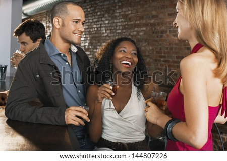 Happy multiethnic couple with friend holding drinks at the bar - stock photo