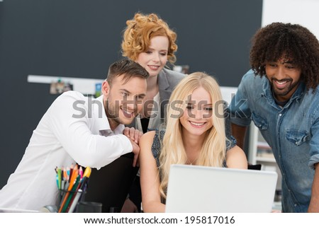 Happy multiethnic diverse group of young business people grouped around a laptop computer smiling as they look at data on the screen - stock photo