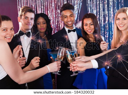 Happy multiethnic friends holding sparkling sticks while toasting drinks at nightclub