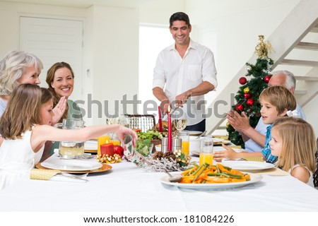 Happy multigeneration family enjoying Christmas meal at dining table - stock photo
